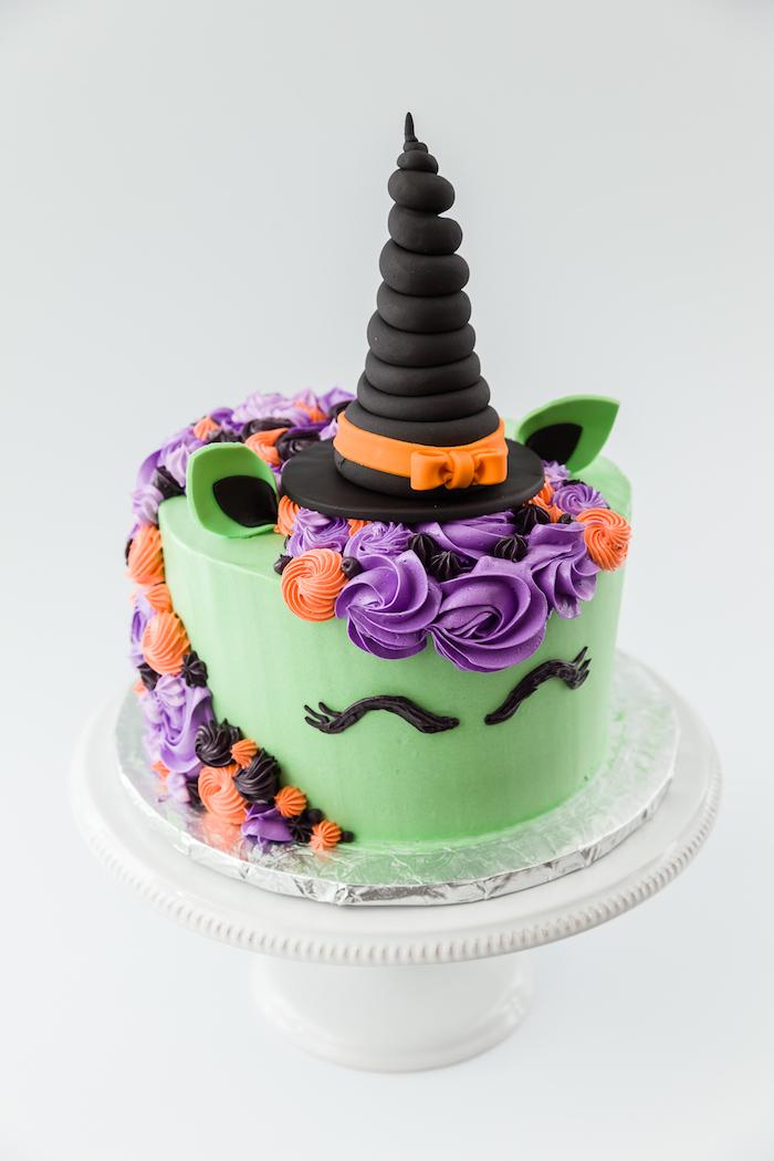 grüne einhorn torte mit schwarzen augen und mit einer mähne aus lila rosen und orangen rosen - ein einhorn mit einem schwarzen hut, ein grünes einhorn mit grünen ohren