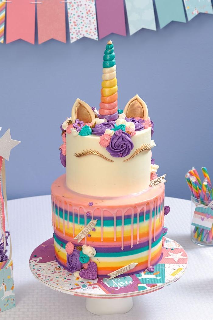 hier ist eine zweistöckige bunte einhorn torte mit einem weißen einhorn und mit einem regenbogenfarbenen horn - mit einer mähne aus lila, blauen und pinken rosen und mit einem lila herzen