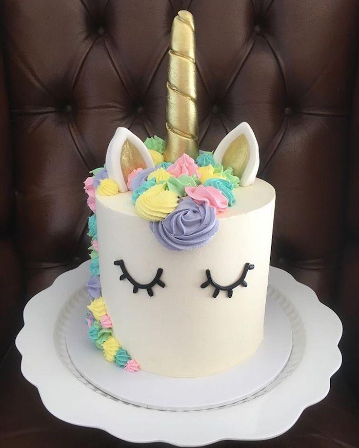 eine weiße fondant torte mit einem einhorn mit schwarzen augen, einer mähne mit lila, pinken und gelben rosen und einem goldenen horn - einhorn torte anleitung