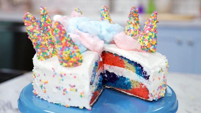 noch eine kleine weiße einhorn torte mit einigen blauen hörnern und einer pinken und einer blauen sahne - idee für einhprn kuchen
