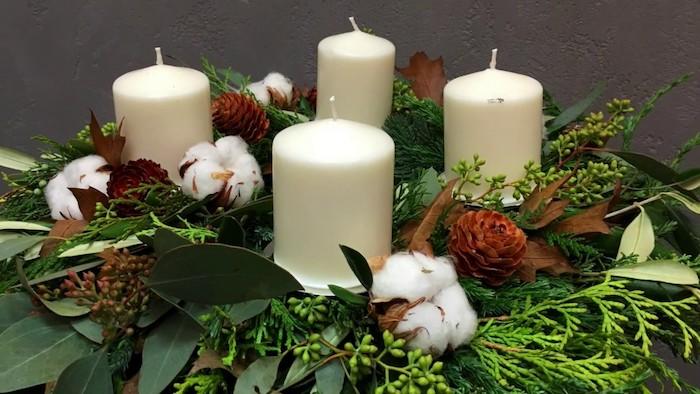 kleiner adventskranz mit watte, vier kleinen weißen sternen, pflanzen mit grünen blättern und kleinen braunen zapfen