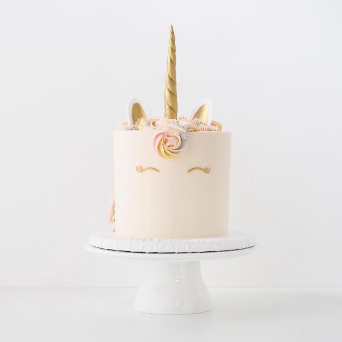 idee für eine pinke einhorn torte mit einem langen goldenen horn und mit goldenen kleinen ohnren znd augen und einer mähne mit großen rosen