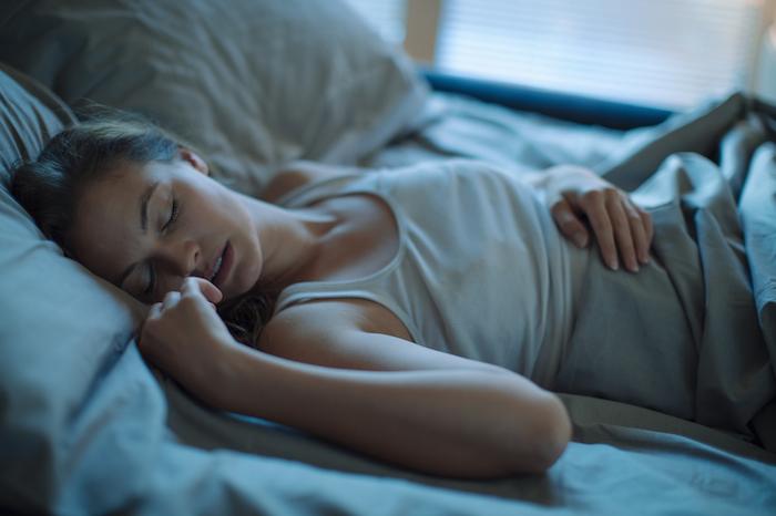 tipps für einen erholsamen schlaf - eine junge schlafende frau - bett mit grauen kissen
