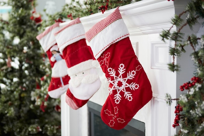 drei rote Nikolaussocken mit Wintermotiven, Socken mit Schneewittchen, Socken mit dem Weihnachtsmann, Socken mit Schneeflocken, offene Feuerstelle, aufgestellter Christbaum