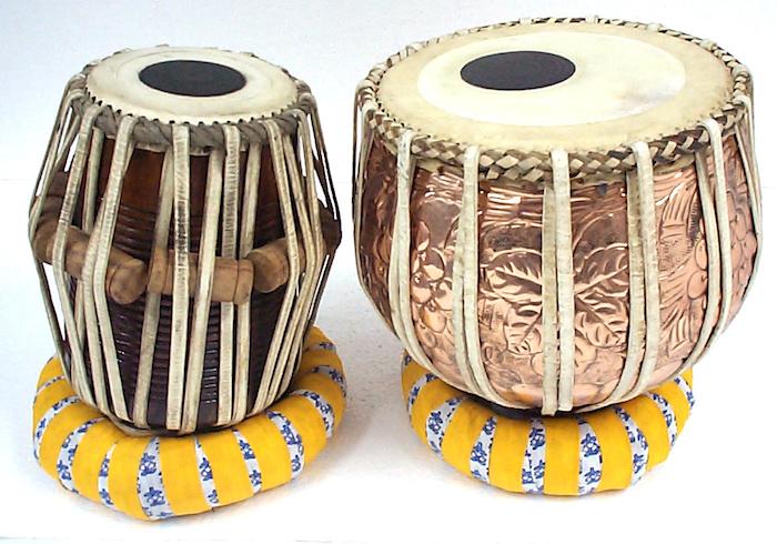 Tabla - links eine Dayan, rechts eine Bayan, Metallkorpusse aus Kupfer, Korpus aus Metalldose, verziert mit Lederriemen, Leder in drei Farben, zwei Ringe aus weißem Stoff mit blauem Blumenprint, eingewickelt mit einem Streifen gelber Stoff