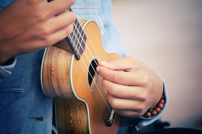 Mini Gitarre mit vier Saiten aus Naturfasern, Decke mit weißen Kanten, Musikspieler mit Denimhemd und Armbändern aus Holzperlen