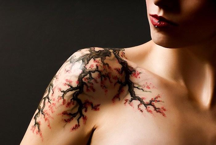 frau mit kirschblüten tattoo am schulter, zweig mi roten blüten
