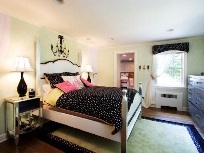 schwarze Bettwäsche, silberne Nachttische und eine Gardine aus Spitze, ein Schrank