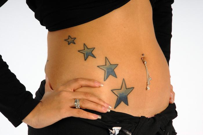 tätowierung mit vier blauen großen sternen - eine junge frau mit stern tattoo - hand mit weinem weißen nagellack und ringen