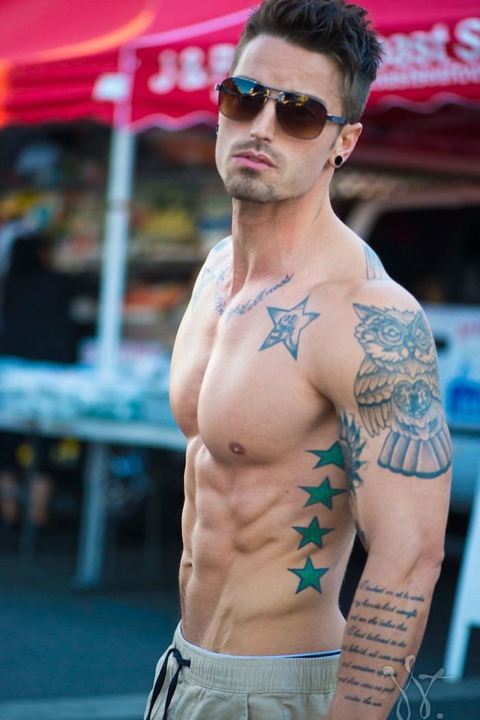 junger mann mit brillen - ein mann mit einem sterne tattoo mit grünen sternen und einem großen tattoo mit eule