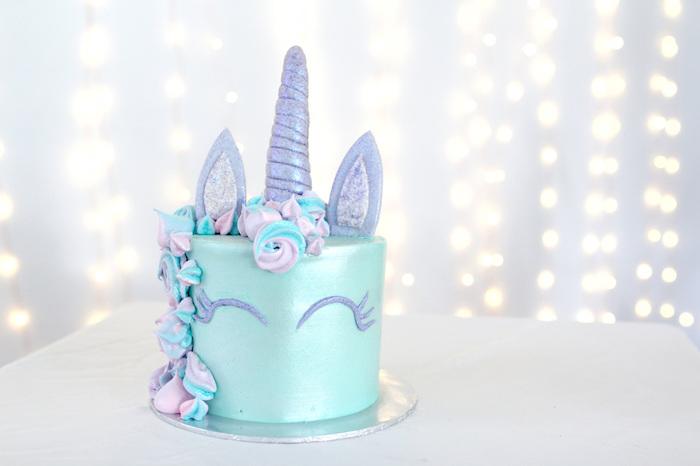 eine schöne blaue torte mit einem blauen einhorn mit einer lila mähne und mit lila augen und mit einem großen langen lila horn und mit langen lila ohren - einhorn miz einer mähne aus lila, blauen und pinken rosen