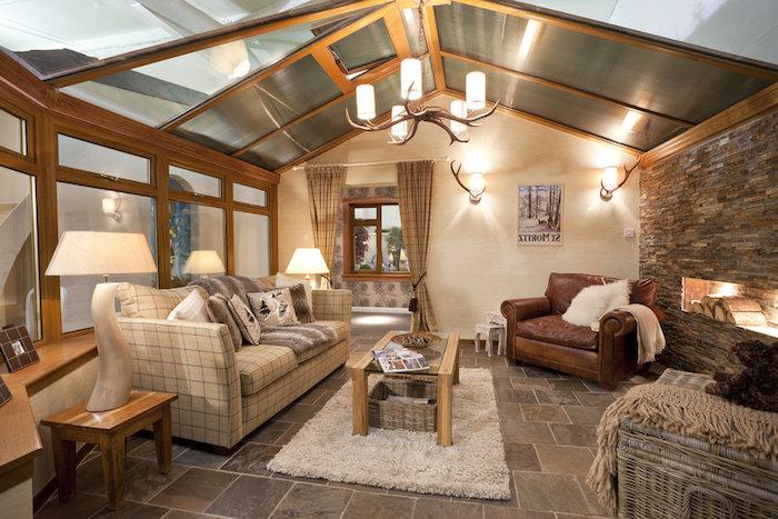 mansardenwohnung robuster stil villa auf dem lande sofa ledersessel hängende lampe teppich glastisch wohndeko wohnideen mansarde