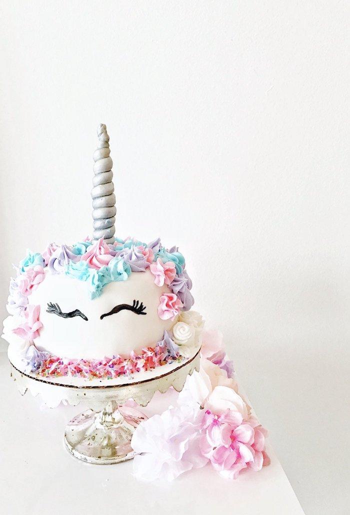 hier ist eine weiße einhorn torte mit einem weißen einhorn und mit schwarzen augen, einem grauen horn und sahne