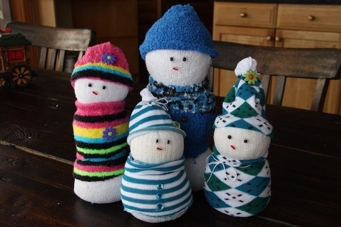 vier weiße schneemänner aus weißen socken und mit schwarzen augen und einer kleinen lila blume und mit hüten - schneemann basteln