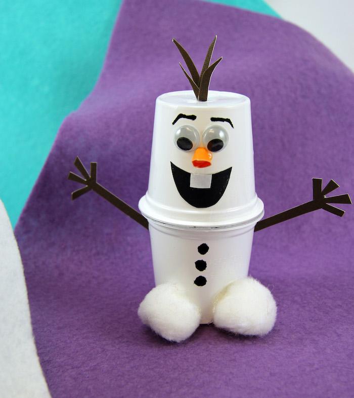 olaf schneemann basteln - ein kleiner weißer schneemann mit drei kleinen schwarzen knöpfen und einer orangen nase - schneemann aus plastikbecker