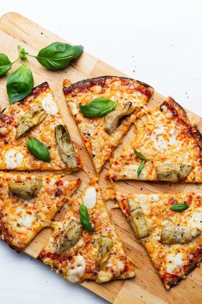 schnelle low carb rezepte pizza aus brokkoli oder blumenkohl gemischt mit eier als unterlage und garniert mit gemüse, bläter basilikum und mozzarella