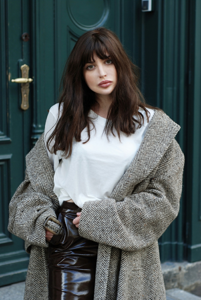 Lange Haare mit Pony, weißes T-Shirt und schwarzer Lederrock, grauer Mantel, natürlicher Look