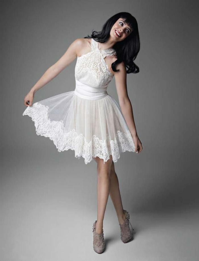 Langhaarfrisur mit Pony, weißes elegantes Kleid mit Spitzenelementen knallrote Lippen und Porzellanteint