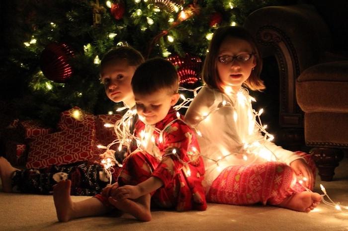 lustige Weihnachten drei niedliche Kinder spielen mit einer Lichterkette vor dem Weihnachtsbaum