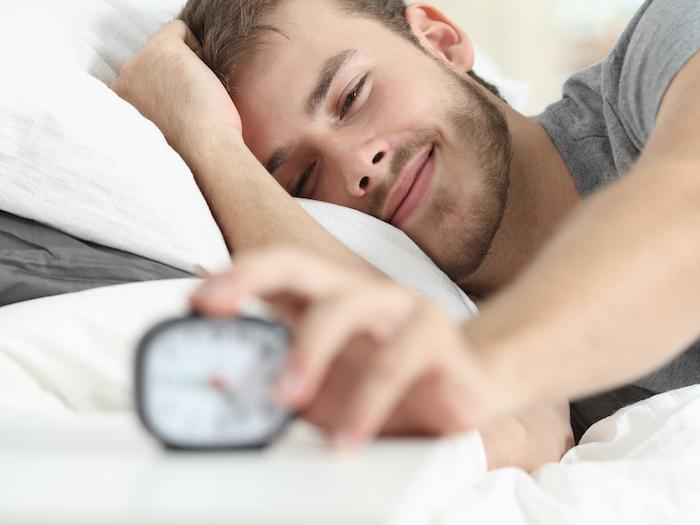 ein junger Mann ist bereits aufgewacht von dem Klingeln eines kleinen Wecker - Guten Morgen Sprüche