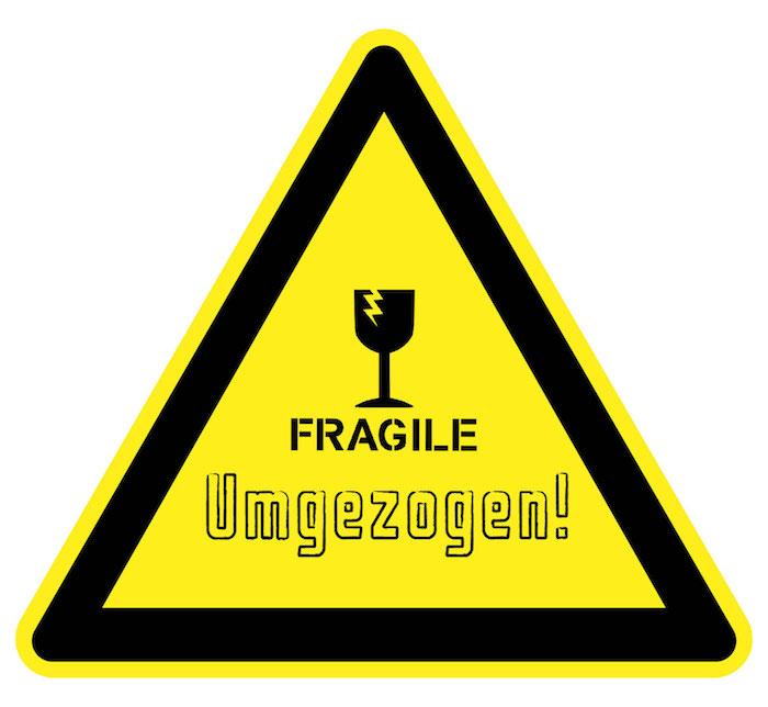 ein lustiger Schild mit der Anschrift: Fragile Umgezogen, gelber Triangel-Schild mit schwarzen Kanten und einem zerbrochenen schwarzen Weinglas