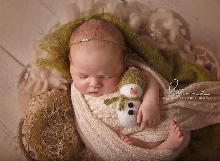 ein Neugeborenes mit dem Spielzeug von Schneemann - lustige Bilder zu Weihnachten