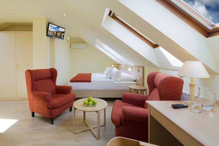 kleine räume geschickt einrichten schlafzimmer und wohnbereich auf einmal kaffeetisch 2 große sessel apfel grün auf dem tisch stehlampe bett fernseher