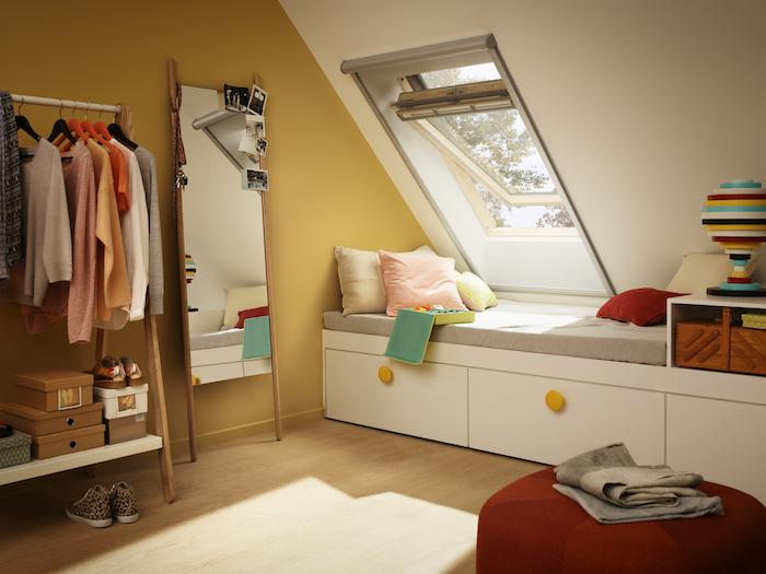 mansardenzimmer teenagerzimmer fenster mit leseecke bücher lesen am fenster großer spiegel kleiderhaken garderobe kasten kisten bodenkissen licht im zimmer