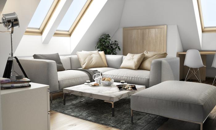 mansardenzimmer wohnzimmer wohnbereich in der maisonette großes graues sofa hocker dekorationen kissen goldene deko grau einrichten