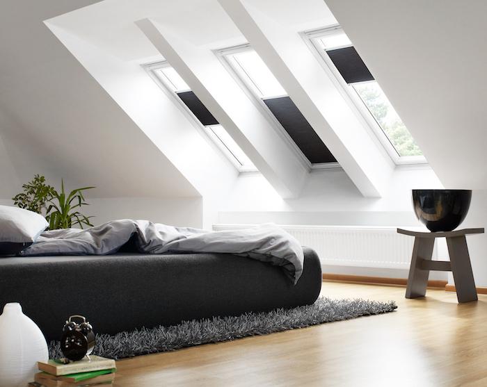dachgeschoss einrichten helles zimmer schlafzimmer mit viel natürlichem licht schwarzes bett fenster hocker vasen deko grauer teppich auf dem boden