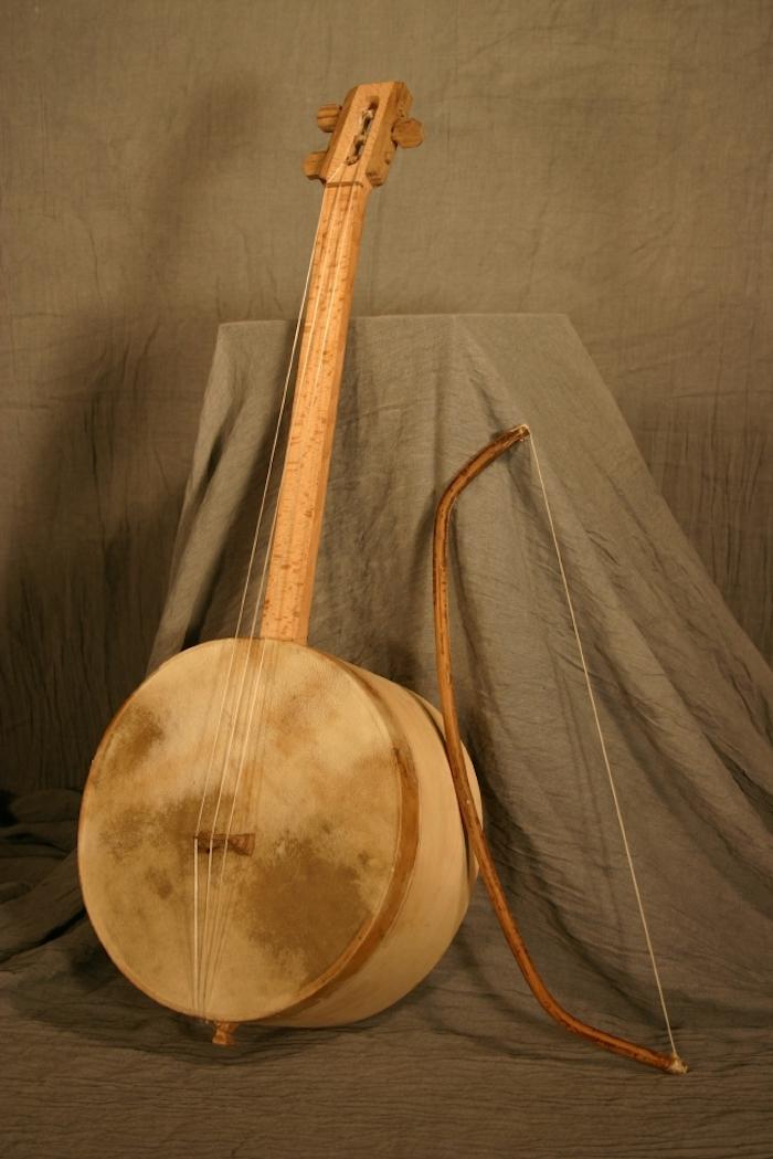 Tschuniri aus Birkenholz mit rundem Korpus, an dem ein Stück Leder mit dunklen Flecken angespannt ist, ein großer Bogen für Bogeninstrumente