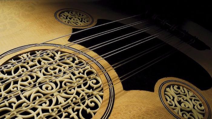 die Decke einer Ukulele, verziert mit Holzschnitzerein und Zeichnungen, zwei Saitenpaare mit Goldfarbe, vier Saitenpaare mit weißer Farbe