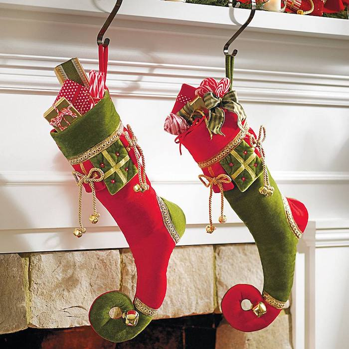 Nikolaus, eine rote und eine grüne Geschenksocke voll mit kleinen Geschenken, Socken, dekoriert mit kleinen Glöckchen und roten Perlen, offener Kamin im Wohnzimmer