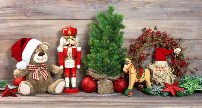 roter Weihnachtsstern, Plüschbär mit rotem Weihnachtshut mit weißem Troddel, Nussknacker aus Holz, kleiner Weihnachtsbaum, Kranz mit Mistelfrüchten, Weihnachtsmannfigur, dekorative grüne Sterne