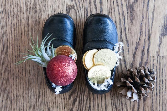 Nikolaus, schwarze Kinderschuhe aus Leder, gefüllt mit Schokomünzen und künstlichem Schnee, roter Weihnachtsbaumkugel mit Glitzer, Zapfen, Parkettboden
