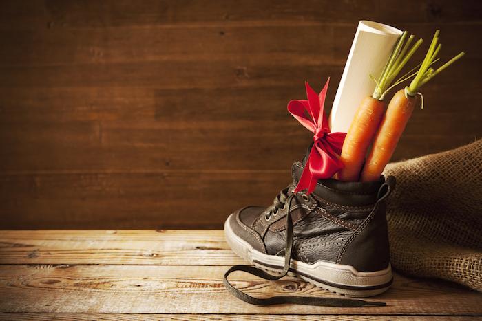 Kinderschuh aus braunem Leder mit braunem Schuhband und weißer Sohle, zwei Möhren, Brief an den Weihnachtsmann mit einer roten Schleife, Holzboden aus Massivholz, Holzwand in dunkler Farbe
