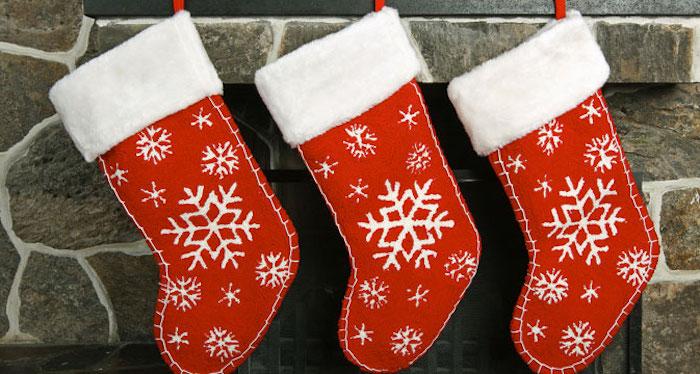 dre rote Socken mit Schneeflocken-Motiv, die auf drei Hacken über dem offenen Kamin hängen, Wand aus Naturstein