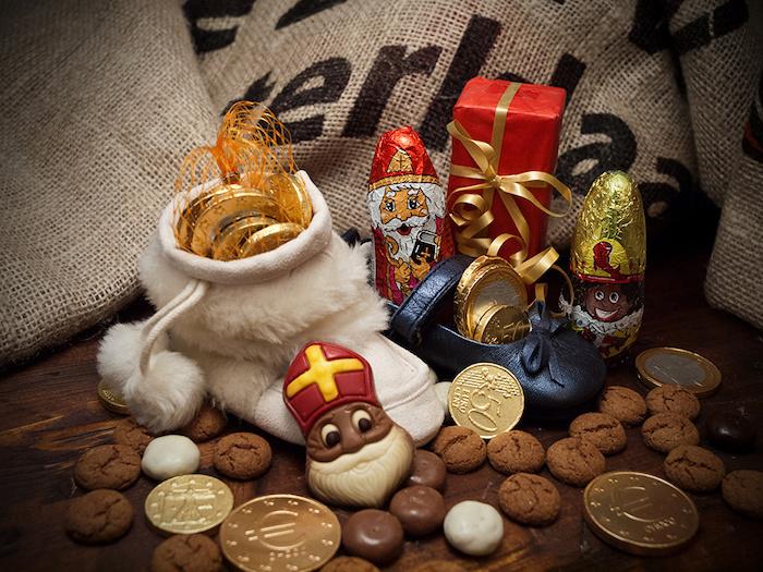drei Säcke voll mit Schokoladenmünzen, Makaronen, Bonbons aus weißer und brauner Schokolade, Schokoladenfiguren, kleines Geschen in rotem Geschenkpapier mit goldener Schleife, Lederschuh in Schwarz, Holzboden