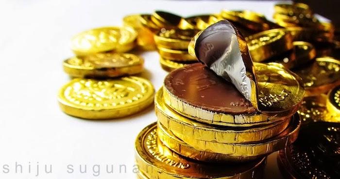 ein Haufen Schokomünzen, gepackt in Folie in Goldfarbe, riesige Goldmünzen, Bild mit weißem Hintergrund
