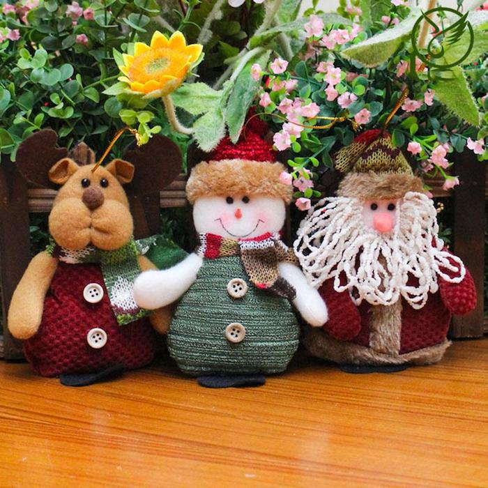 drei Strickfiguren - Rudolph mit einem roten Mantel mit weißen Knöpfen, ein lächelnder Schneemann mit rotem Winterhut, kariertem Schal und grünem Mantel mit grauen Knöpfen, der Weihnachtsmann mit roter Nase, künstliche Blumen, echte Pflanzen, Holztisch mit Lack