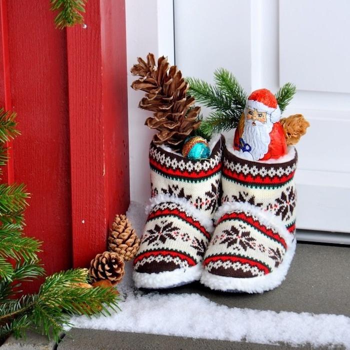 Kinderschuhe für Zuhause mit Wintermotiven, gefüllt mit Zapfen und Schokoladenfiguren, weißer Holztür, roter Holzwand, Schnee vor der Eingangstür