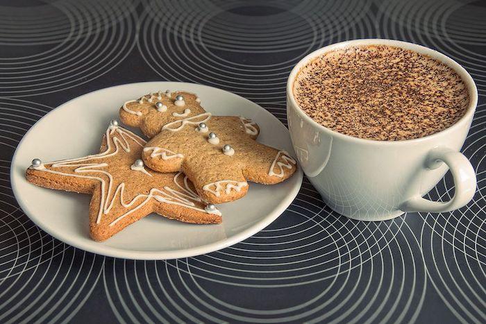 zwei Lebkuchen mit Zimt, dekoriert mit Zuckerperlen mit silberner Farbe, weiße Kaffeetasse mit Kaffeeteller, warmes Getränk mit Milch und Schokolade, dunkelgraue Tischdecke mit weißen Kreisen