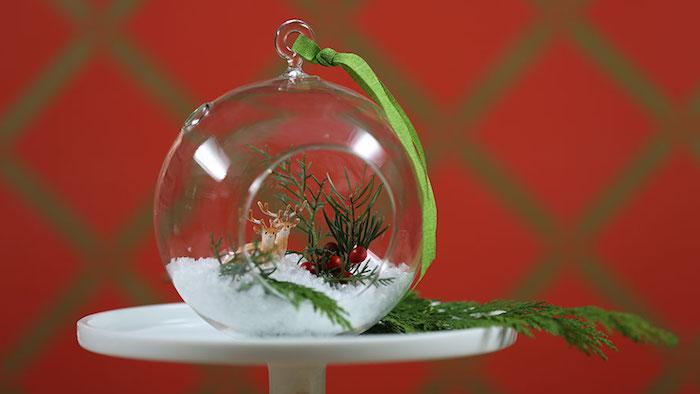 Glaskugel für Weihnachtsbaum mit rundem Loch, Miniatur von Elchen, kleine rote Beeren, Zweig vom Weihnachtsbaum, rote Tapeten mit grünem Muster