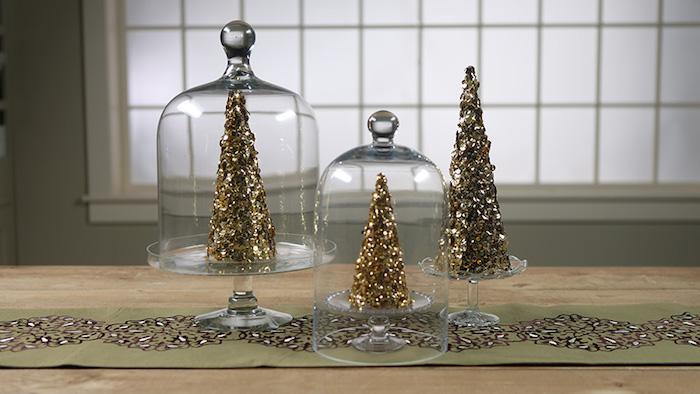 drei Tortenteller aus Glas, zwei Glasglocken, Tischläufer mit Print, drei dekorative Weihnachtsbäume mit Goldglitzer, großes Fenster mit Mattglas