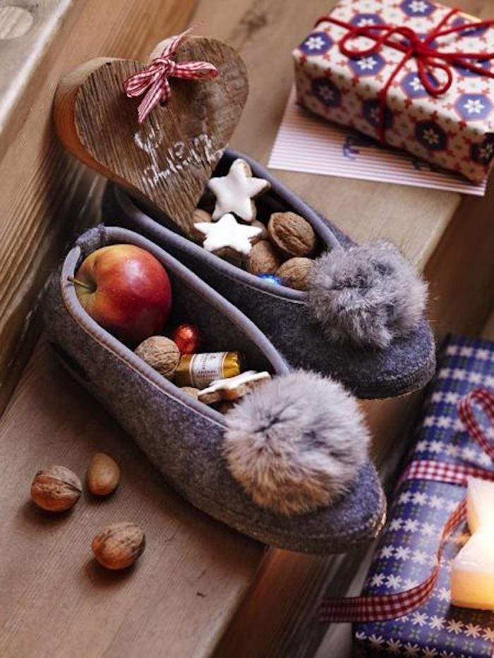 Pantoffel mit Troddel in grauer Farbe, Herzdeko aus Holz, kleines Geschenk in Papier mit Schneeflocken-Motiven, Kerze in der Form eines Sternes, Holztreppen, Weihnachtskarte, drei Walnüsse
