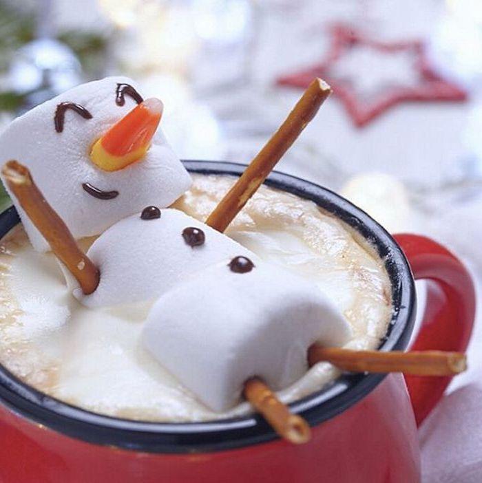 warmes Kaffeegetränk mit geschlagener Milch, Marshmallow-Schneemann mit Armen und Beinen aus Salzstangen, rote Kaffeetasse mit schwarzem Kant