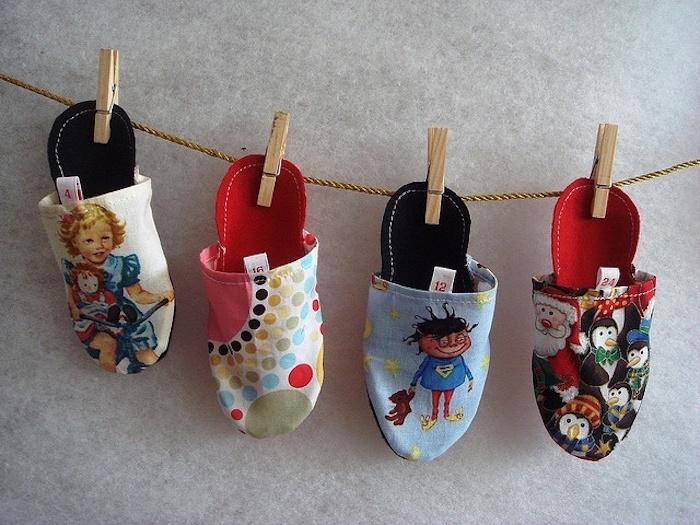 vier Pantoffel mit Weihnatchsprint, die auf einem Seil mit Holzklammern zum Nikolaustag gehängt sind