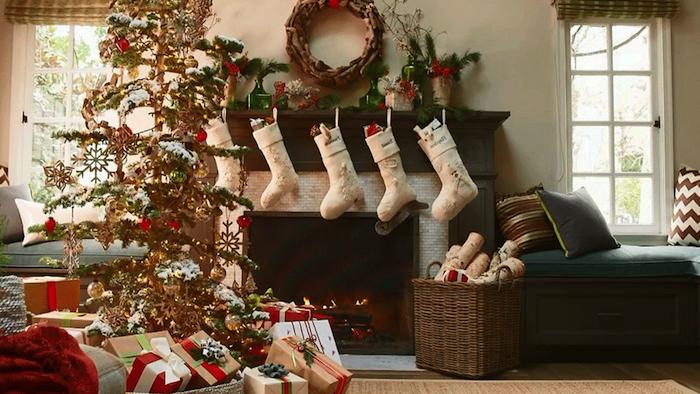 Haus mit zwei Leseecken vor dem Fenster, weiche Kissen mit Musterbezügen, Flechtkorb voller Spielzeuge, weiße Nikolaussocken, die über der offenen Feuerstelle hängen, echter Weihnachtsbaum mit vielen Geschenken darunter, Deko mit Nadelbaumzweigen, großer Kranz, dunkler Parkettboden, Teppich in Beige
