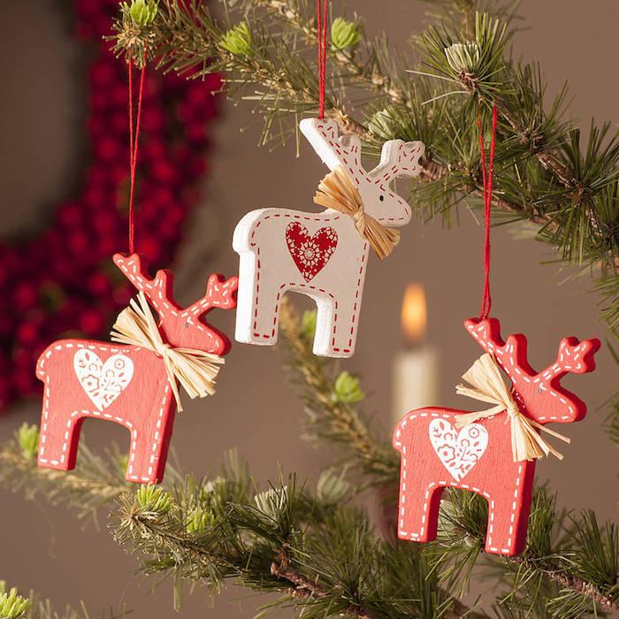 Weihnachtsbaum mit zwei roten und einem weißen Elchen aus Karton, Weihnachtsdeko mit Herzen, roter Kranz an der Wand