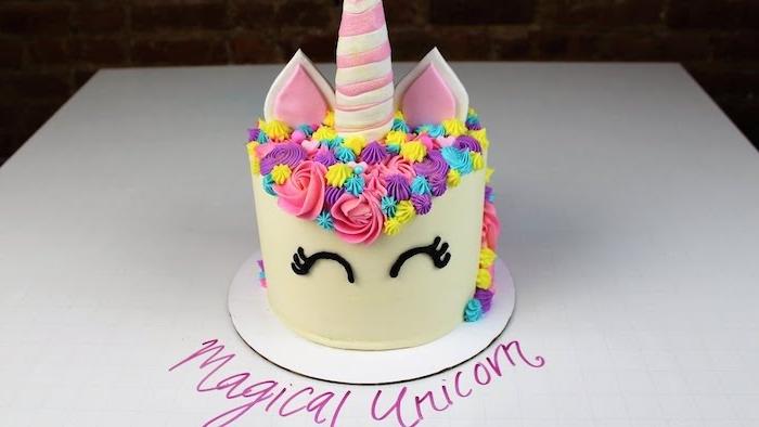 hier ist eine torte mit einem weißen einhorn - einhorn torte mit einer regenbogenfarbenen mähne mit pinken großen rosen, kleine gelben rosen und kleinen blauen rosen